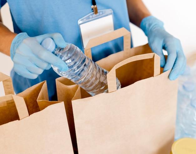 Alto ângulo da pessoa colocando água em sacos de doação