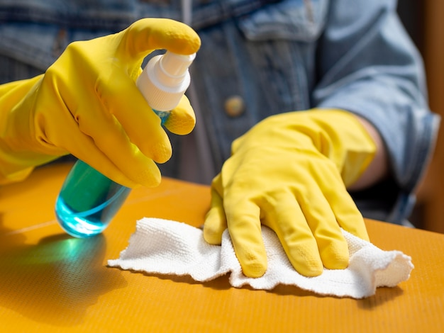 Alto ângulo da pessoa com luvas cirúrgicas, limpando a superfície com álcool e guardanapo