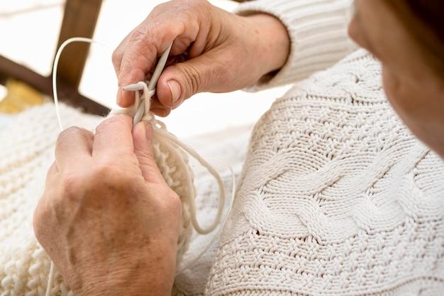 Alto ângulo da pessoa fazendo crochê com fios