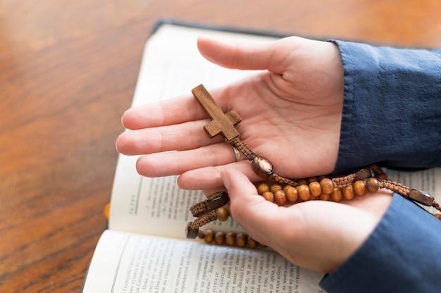 Alto ângulo da pessoa segurando o rosário com livro sagrado aberto