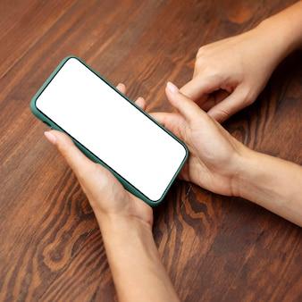 Alto ângulo das mãos de mulheres segurando um smartphone
