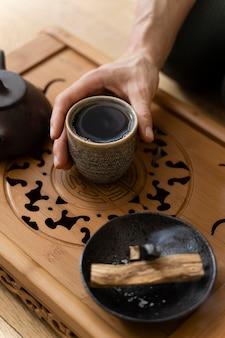Alto ângulo das mãos de uma mulher com uma xícara de chá e uma chaleira