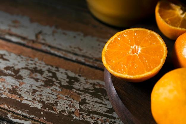 Alto ângulo das metades da laranja do outono no prato com espaço de cópia