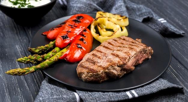 Alto ângulo de bife no prato com legumes