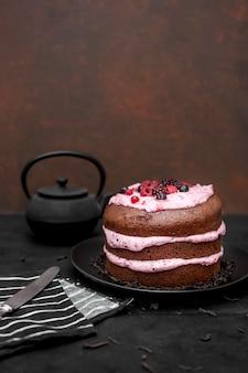 Alto ângulo de bolo com espaço para texto e bule de chá