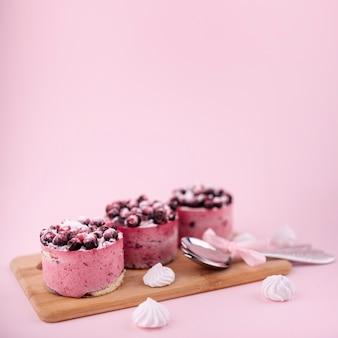 Alto ângulo de bolos de frutas com colher e copie o espaço