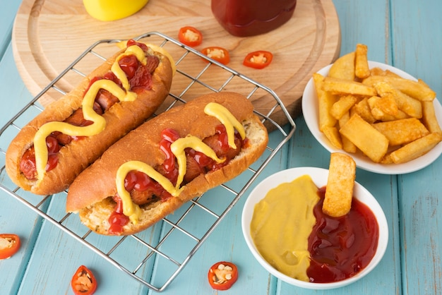 Alto ângulo de cachorro-quente com batatas e ketchup e mostarda