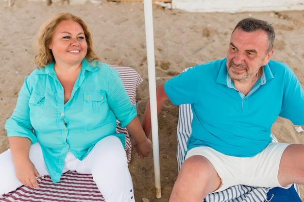 Alto ângulo de casal de turistas mais velhos na praia