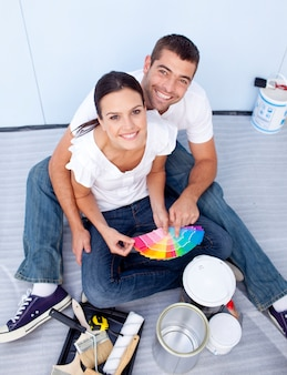 Alto ângulo de casal selecionando cores para pintar nova casa