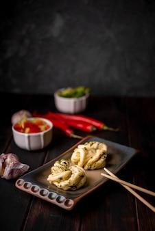 Alto ângulo de comida asiática no prato com pauzinhos
