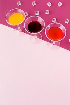 Alto ângulo de copos de cocktails com cubos de gelo e espaço para texto