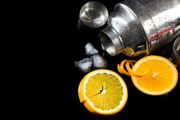 Alto ângulo de coqueteleira com laranja e copie o espaço