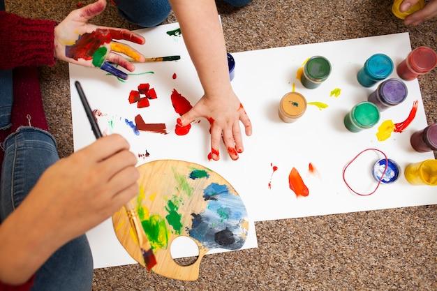 Alto ângulo de criança e mulher pintura
