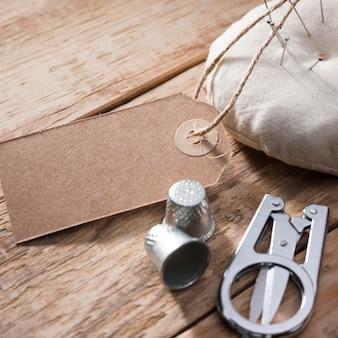 Alto ângulo de dedais com tesoura e etiqueta