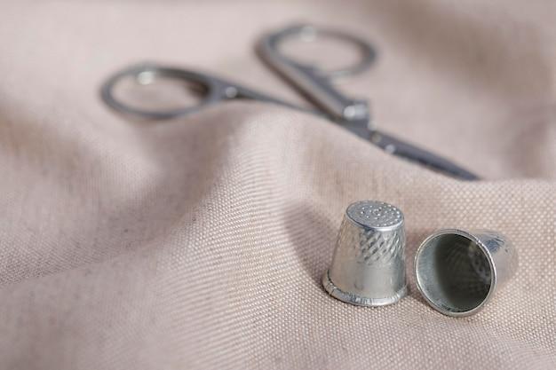Alto ângulo de dedais com uma tesoura em têxteis