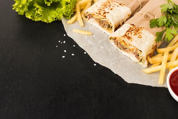 Alto ângulo de delicioso kebab com batatas fritas e espaço de cópia