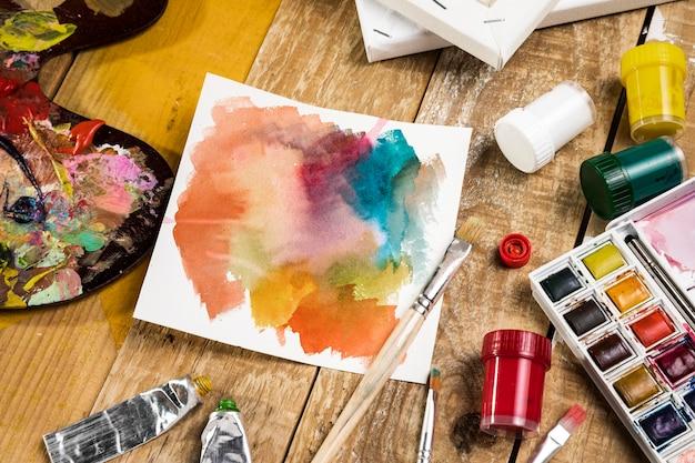 Alto ângulo de elementos essenciais de pintura com paleta e papel