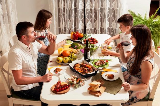 Alto ângulo de família comendo na mesa de jantar