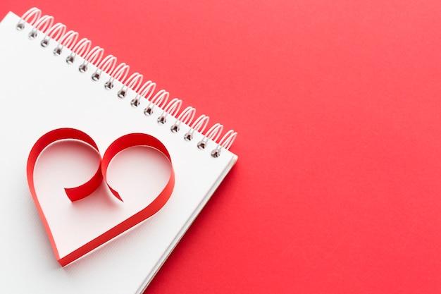 Alto ângulo de forma de coração de papel no notebook com espaço de cópia