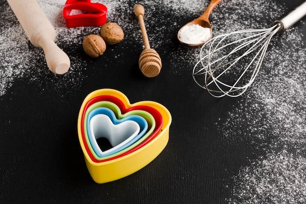 Alto ângulo de formas de coração colorido com utensílios de cozinha
