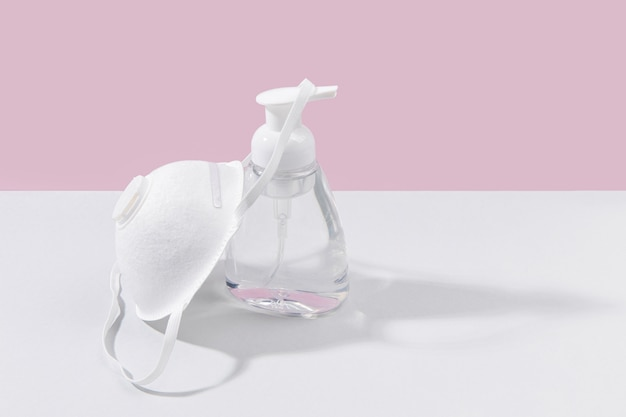 Alto ângulo de garrafa desinfetante para as mãos com espaço para máscara facial e cópia