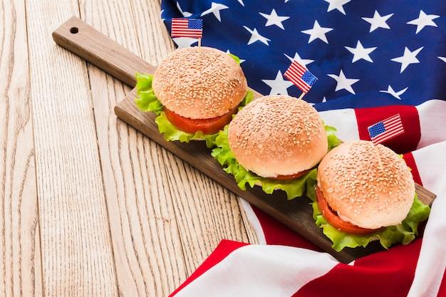 Alto ângulo de hambúrgueres com bandeiras americanas na superfície de madeira