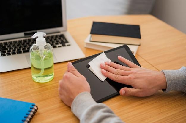 Alto ângulo de homem desinfetar seu tablet antes da aula