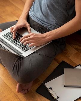 Alto ângulo de homem usando laptop em casa em quarentena para trabalhar