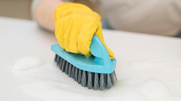 Alto ângulo de limpeza de mulher enquanto segura a escova