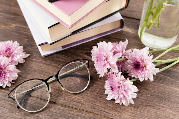 Alto ângulo de livros flores e copos na mesa de madeira