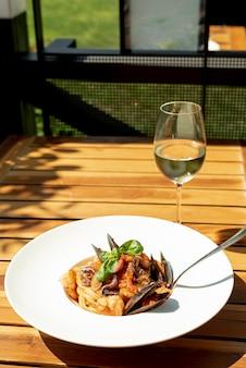 Alto ângulo de macarrão e vinho na mesa de madeira