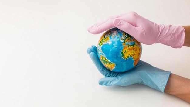 Alto ângulo de mãos com luvas segurando o globo com espaço de cópia