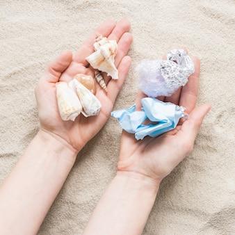 Alto ângulo de mãos segurando conchas e plástico