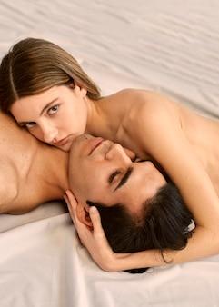 Alto ângulo de mulher bonita e homem sem camisa na cama