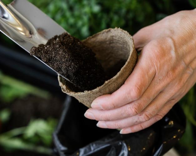 Alto ângulo de mulher colocando terra em um vaso para o plantio