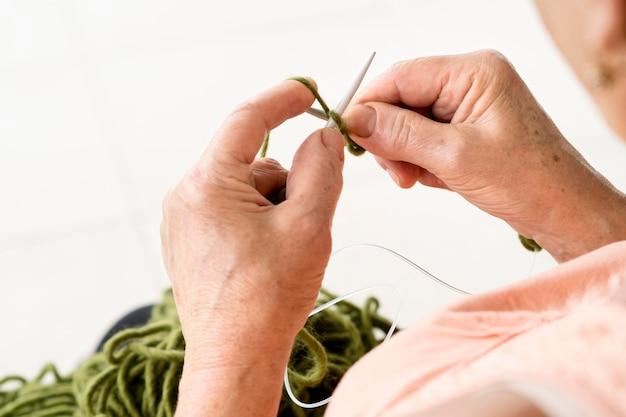 Alto ângulo de mulher com agulha de crochê