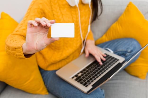 Alto ângulo de mulher com o laptop no colo, mostrando o cartão de crédito