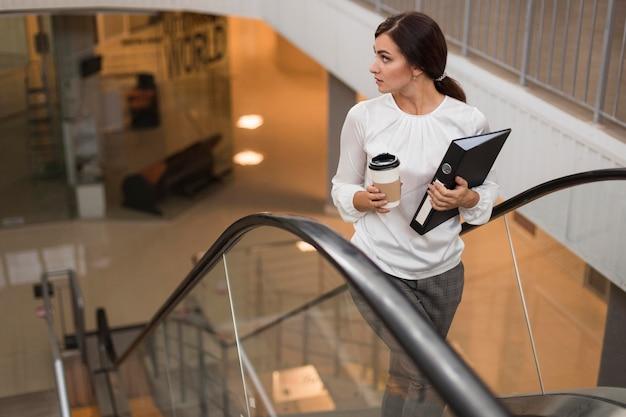 Alto ângulo de mulher de negócios com pasta e café na escada rolante