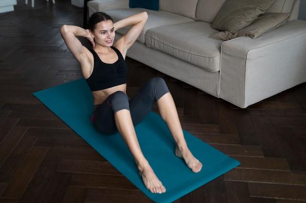 Alto ângulo de mulher em athleisure exercitando na esteira da ioga