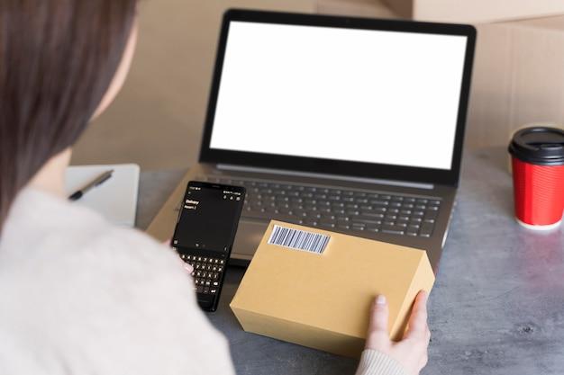 Alto ângulo de mulher olhando para o código de barras na caixa que ela está segurando