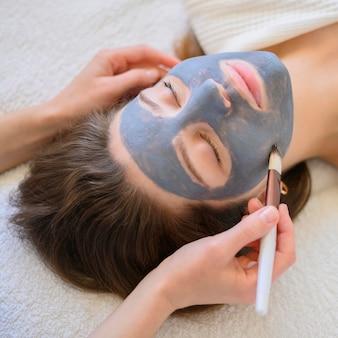 Alto ângulo de mulher recebendo uma máscara facial