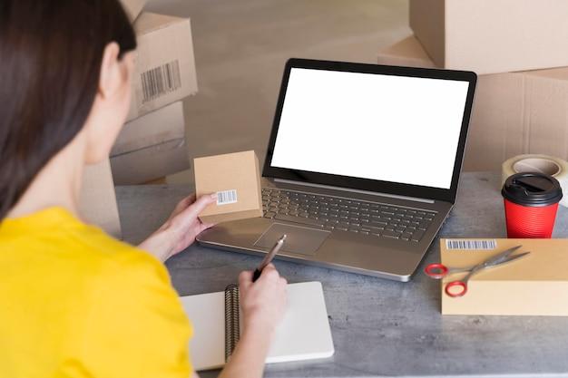 Alto ângulo de mulher segurando a caixa com código de barras e trabalhando
