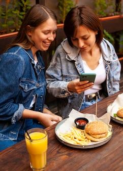 Alto ângulo de mulheres tirando fotos de sua comida