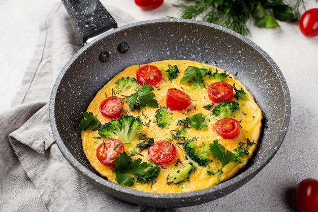 Alto ângulo de omelete de café da manhã na panela com tomates e ervas
