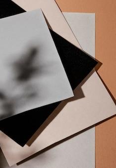 Alto ângulo de papéis com sombra de folhas