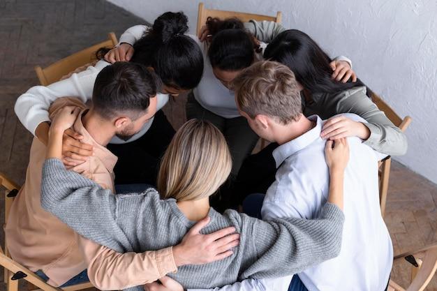 Alto ângulo de pessoas abraçadas em um círculo em uma sessão de terapia de grupo