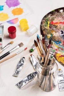 Alto ângulo de pincéis de pintura em jar e paleta