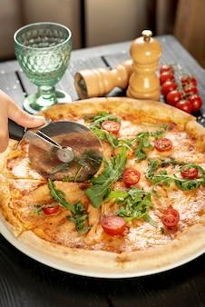 Alto ângulo de pizza de corte de mão na mesa de madeira