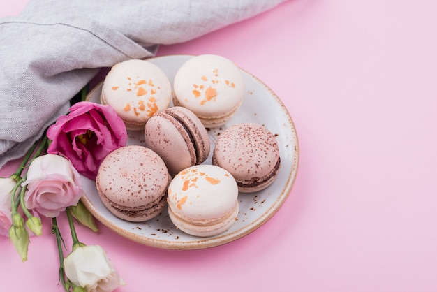 Alto ângulo de prato com macarons e rosas