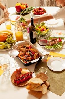 Alto ângulo de pratos com vinho na mesa de jantar